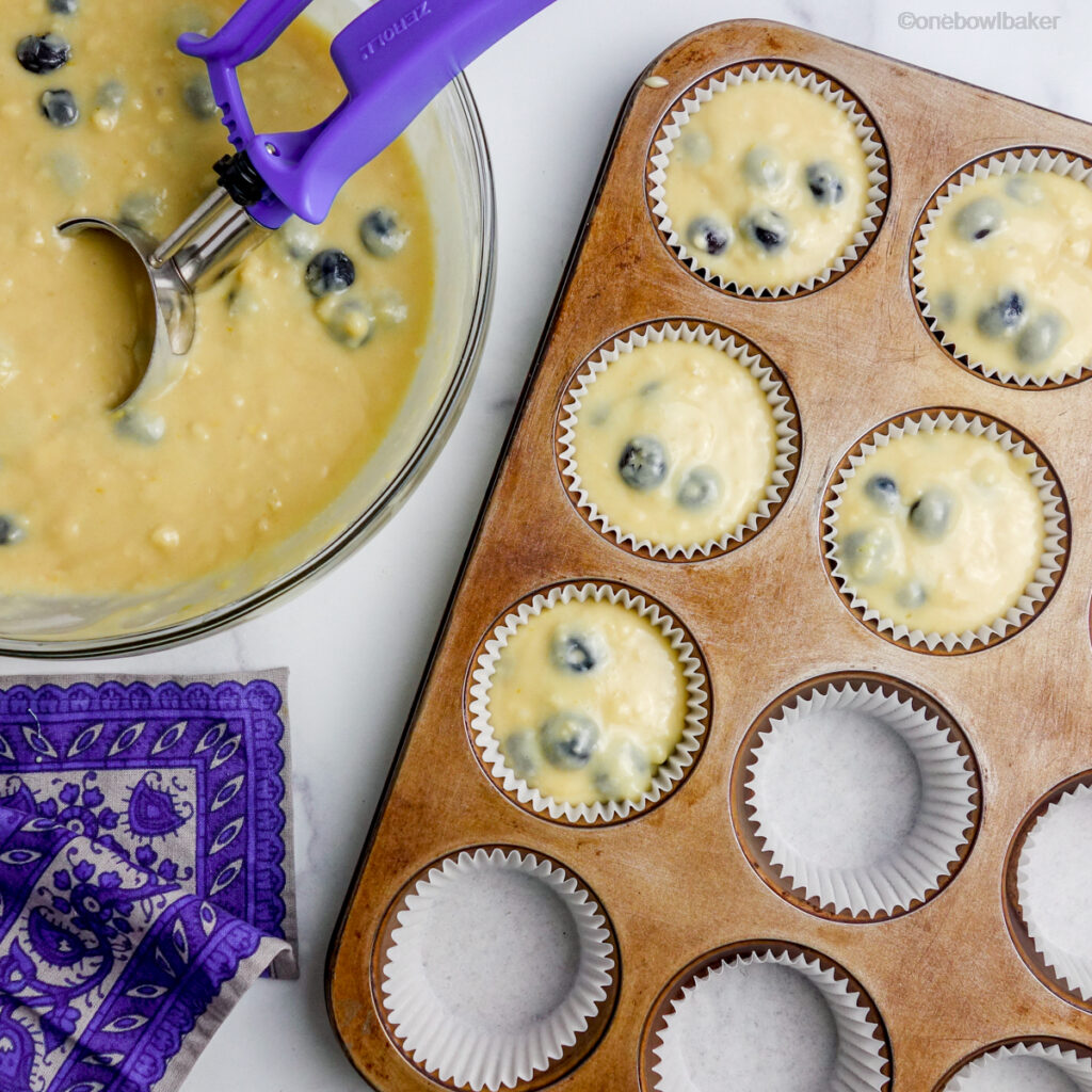 overhead shot of blueberry muffin batter being scooped into prepared muffin cups