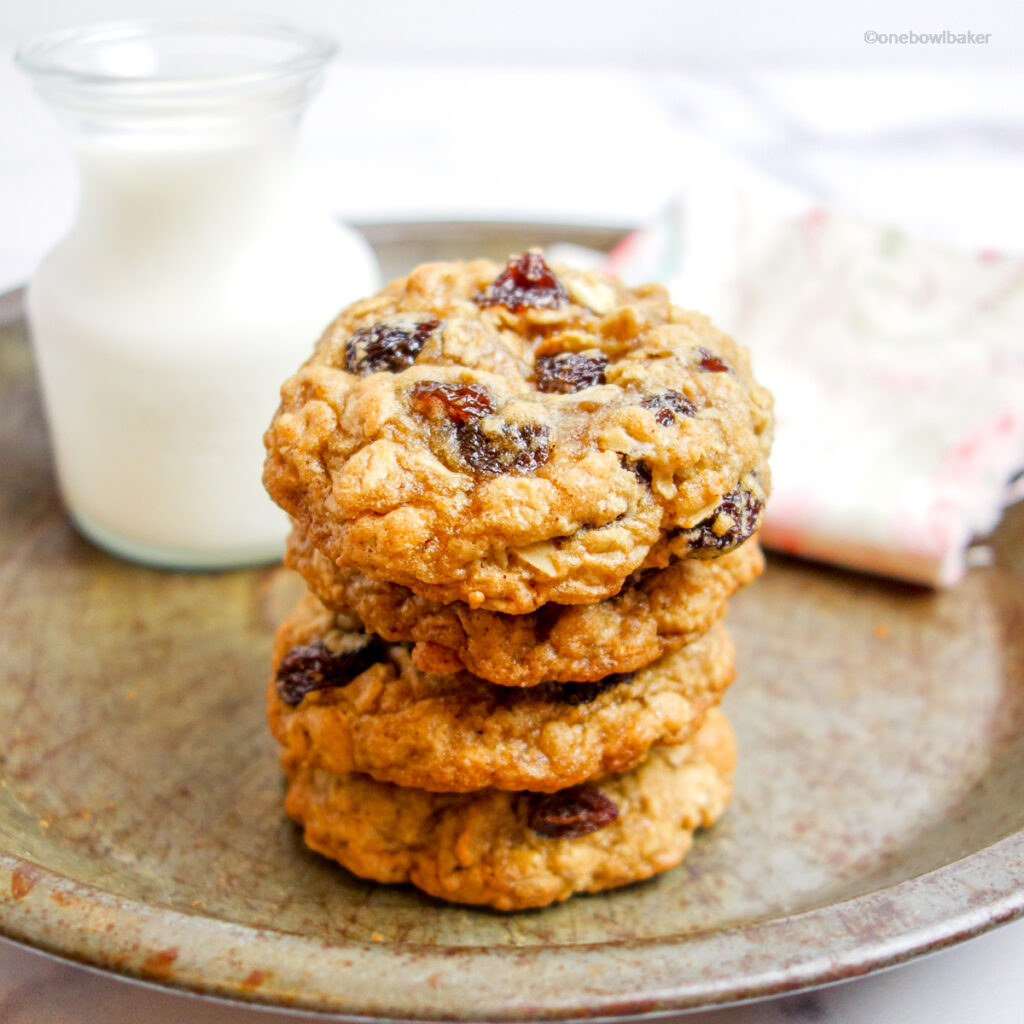 a stack of oatmeal raisin cookies on an antique pie plate