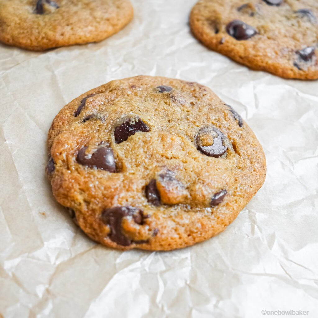 freshly baked banana chocolate chip cookies on a parchment paper lined baking sheet