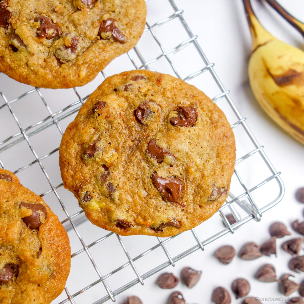banana chocolate chip cookies on a cooling rack with bananas and chocolate chips in the background