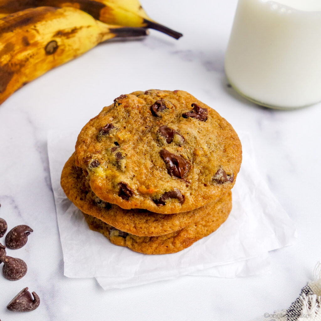 stack of 3 banana chocolate chip cookies on white parchment paper, with milk, bananas and chocolate chips in the background