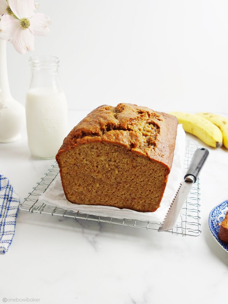 loaf of banana bread with bananas, anda jug of milk, in the background