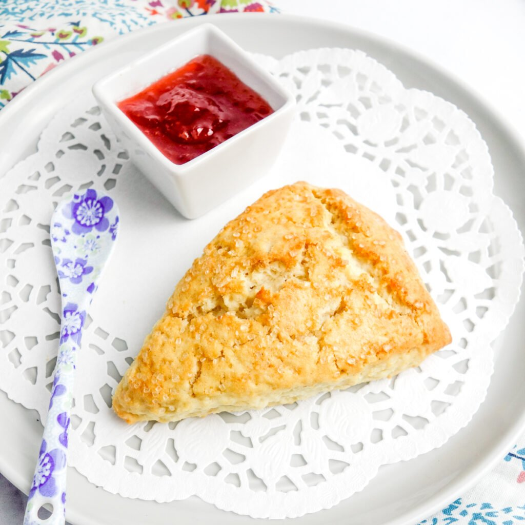 cream scone on a doily-lined grey plate