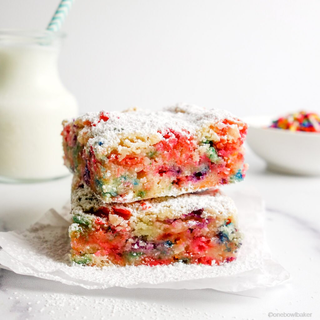 a stack of two funfetti blondies ona white parchment paper, with milk and a bowl of funfetti into the background