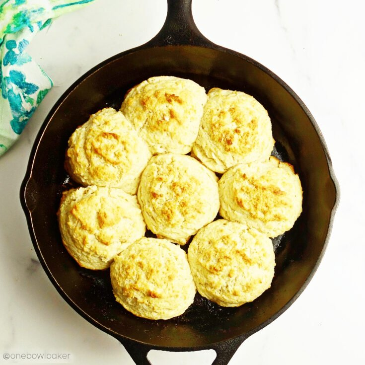 overhead shot of a cast iron skillet filled with buttery drop biscuits